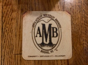 A coaster from Appalachian Mountain Brewery that lists the three pillars of Community, sustainability and philanthropy