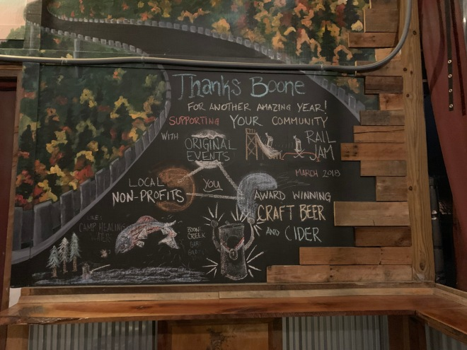 A chalk wall at AMB that lists its nonprofits, supported by events and beer sales