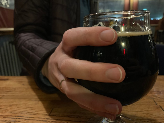 A hand on a pint glass of beer from AMB