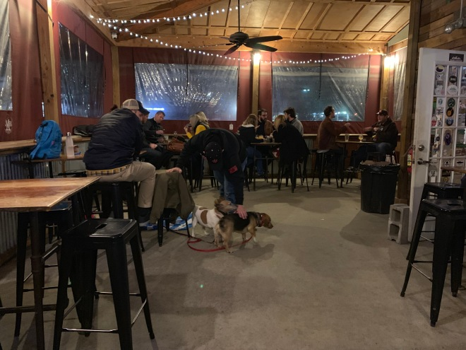 Groups of people sit at tables at Appalachian Mountain Brewery's patio area