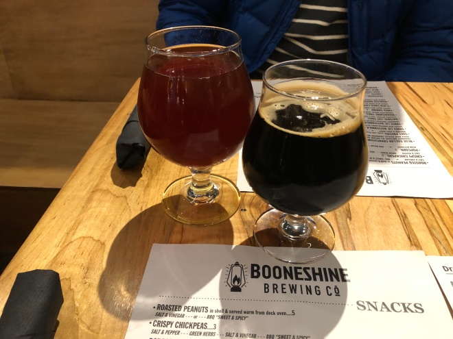 Two beers sit on a table at Booneshine. The menu lists snacks and appetizers.