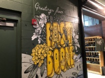 "A mural on the wall reads ""Greetings from East Boone"""