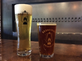 Two glasses of beer sit at Booneshine's bar. Taps are in the background.
